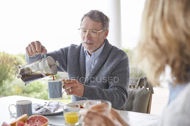 Uomo anziano versando il caffè dalla stampa francese sul patio — Foto stock