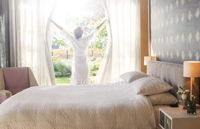 Mujer en bata de baño apertura de cortinas de dormitorio - foto de stock