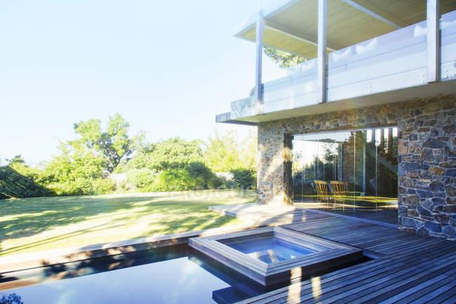 Casa moderna con vista sulla piscina e sul ponte di legno — Foto stock