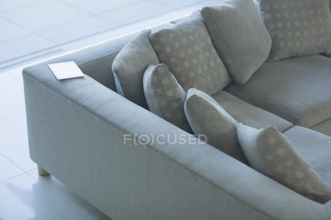 Цифровой планшет на секционном диване — стоковое фото