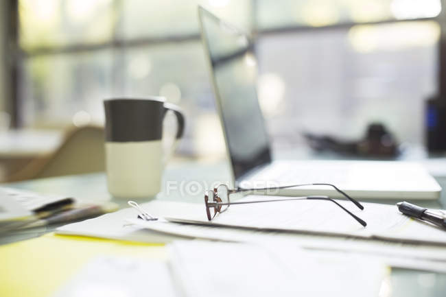 Close up of coffee cup and eyeglasses on paperwork near laptop — Stock Photo