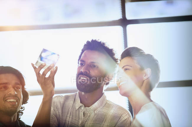 Curious, innovative entrepreneurs examining glass cube prototype — Stock Photo