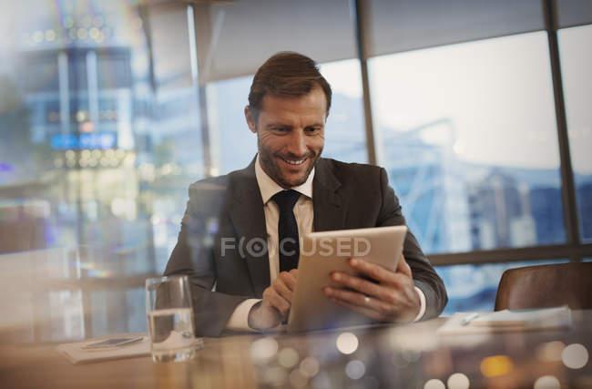 Uomo d'affari sorridente che utilizza tablet digitale in sala conferenze — Foto stock