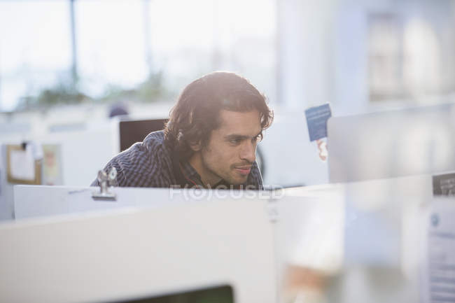 Focused businessman working at computer in office cubicle — Stock Photo