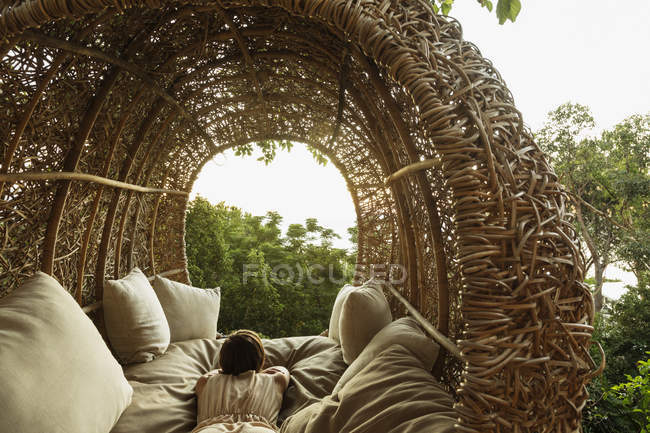 Woman laying in nest tree house — Stock Photo