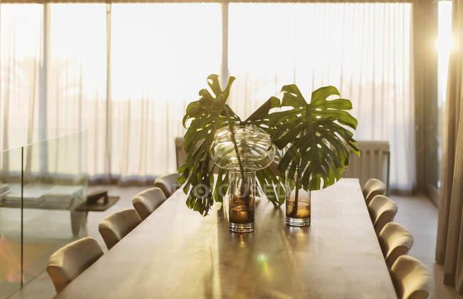 Тропічний завод листя в вази на обідній стіл — стокове фото