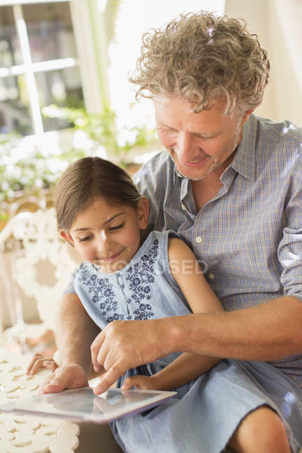 Grandfather and granddaughter using digital tablet together — Stock Photo