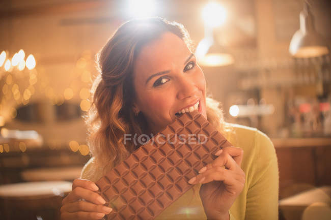 Portrait woman with sweet tooth craving biting into large chocolate bar — Stock Photo