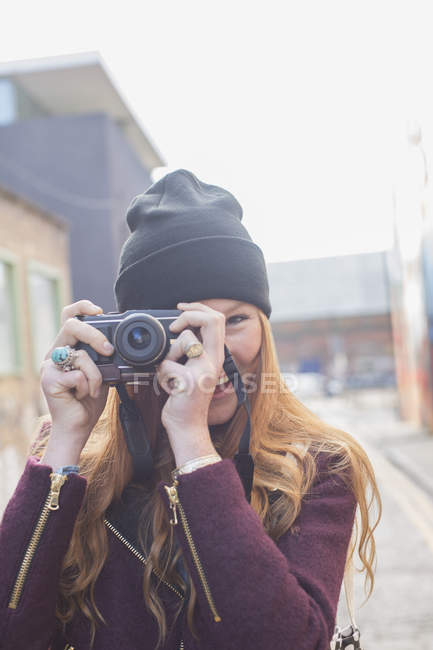 Happy young woman using camera on city street — Stock Photo