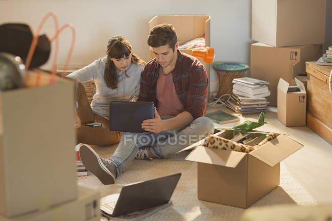 Pareja joven usando laptop rodeado de cajas de mudanza - foto de stock