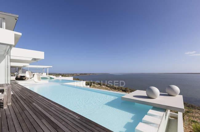 Sunny, tranquillo moderno lusso casa vetrina piscina a sfioro esterna con vista sull'oceano sotto il cielo blu — Foto stock