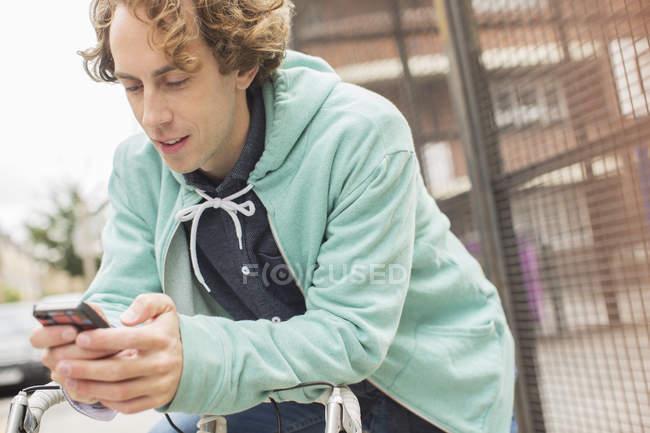 Heureux jeune homme utilisant téléphone portable sur vélo — Photo de stock
