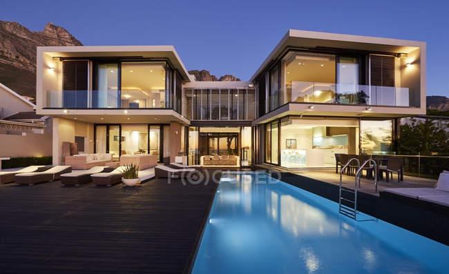Moderna casa de luxo vitrine exterior e piscina iluminada à noite — Fotografia de Stock