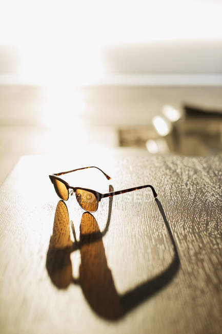 Sunglasses casting shadow on table — Stock Photo