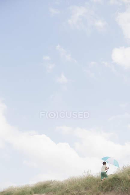Ragazzo con ombrellone a strisce che cammina in spiaggia erba sotto il cielo blu estivo — Foto stock