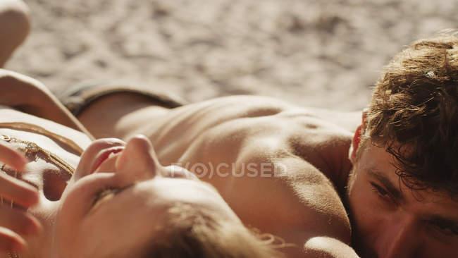 Jovem casal se bronzear na praia ensolarada — Fotografia de Stock
