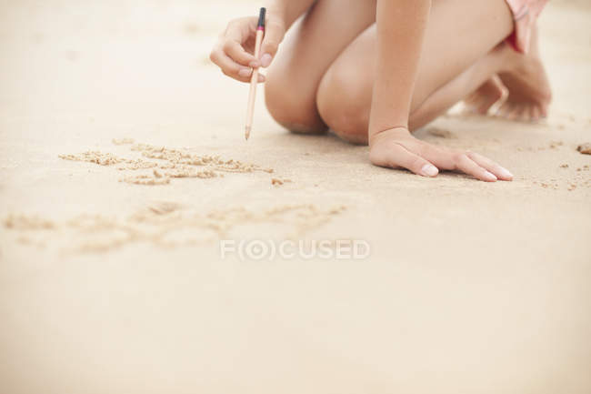 Girl with pencil writing in sand on summer beach — Stock Photo