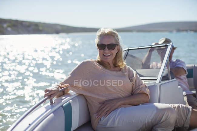 Літня жінка, що сидить у човні на воді — стокове фото
