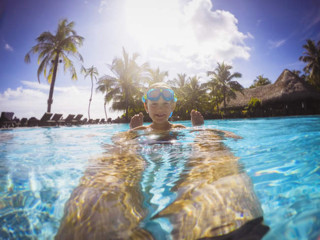 Portrait smiling boy in sunny tropical swimming pool — Stock Photo