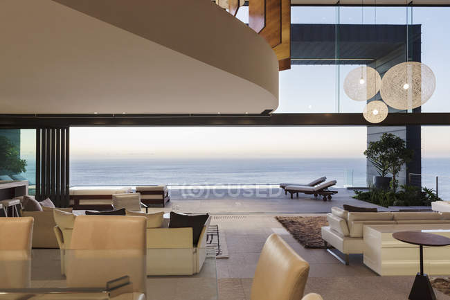 Modern living room overlooking ocean at sunset — Stock Photo
