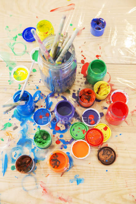 Jars of paint and paintbrushes on wooden table — Stock Photo