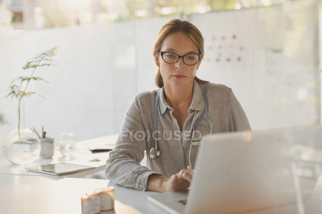 Focused female doctor working at laptop in doctors office — Stock Photo