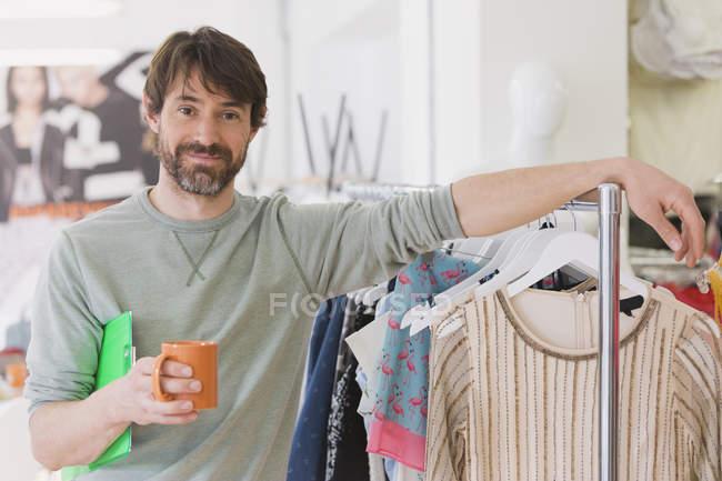 Retrato confiado comprador de moda masculina beber café apoyado en rack - foto de stock