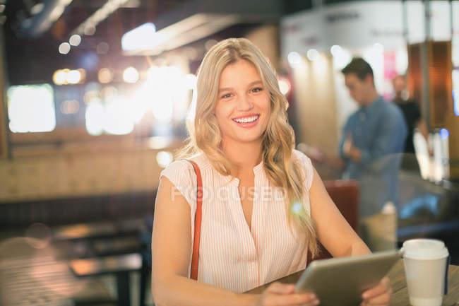 Ritratto giovane donna sorridente utilizzando tablet digitale al caffè — Foto stock
