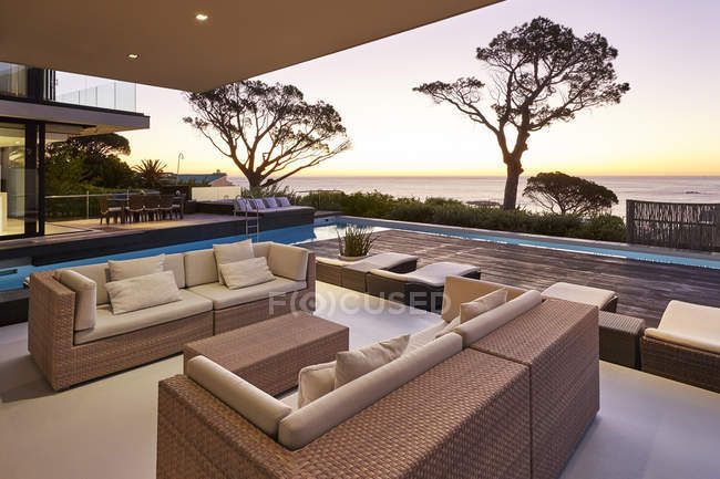 Moderna casa de luxo vitrine pátio e piscina com vista para o mar ao pôr do sol — Fotografia de Stock