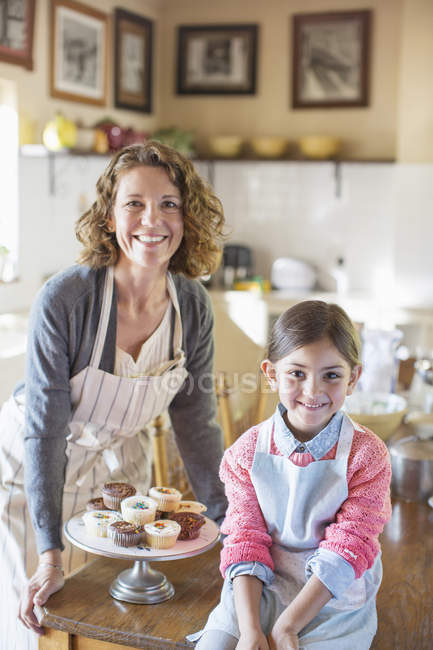 Happy beautiful grandmother and granddaughter smiling in kitchen — Stock Photo