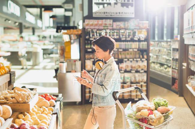 Молода жінка з навушниками, за допомогою мобільного телефону, покупка продуктів на ринку — стокове фото