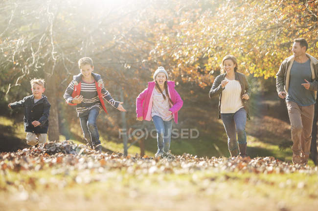 Family running in park with autumn leaves — Stock Photo