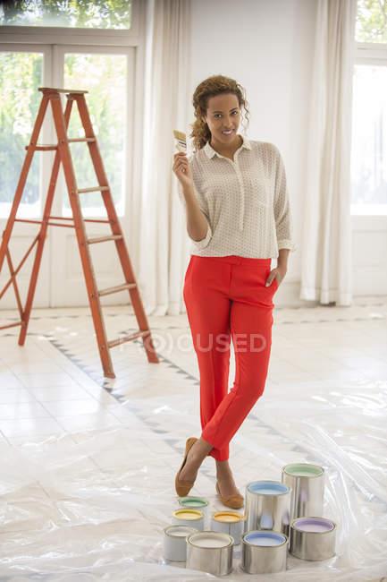Женщина держит кисть возле банки с краской — стоковое фото