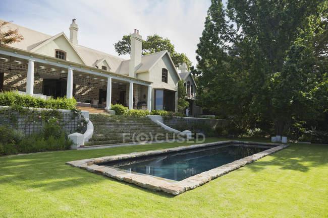 Pool under trees against luxury modern house — Stock Photo