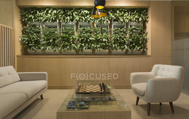 Lounge with plant display, chessboard and seating — Stock Photo