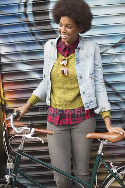 Mujer sosteniendo bicicleta frente a la pared de graffiti - foto de stock