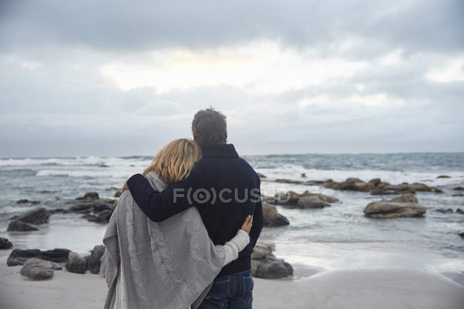 Serene affectionate couple hugging on winter beach looking at ocean — Stock Photo