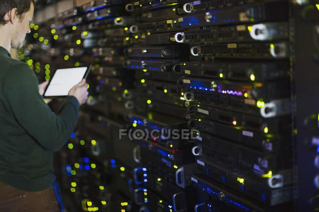 Техник номер сервера, с помощью цифрового планшета на панели — стоковое фото