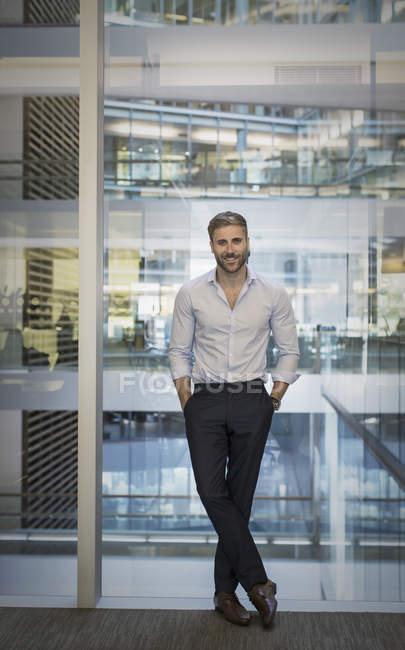 Uomo d'affari sicuro ritratto alla finestra dell'ufficio — Foto stock
