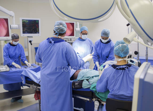 Team of doctors performing surgery in operating theater — стоковое фото