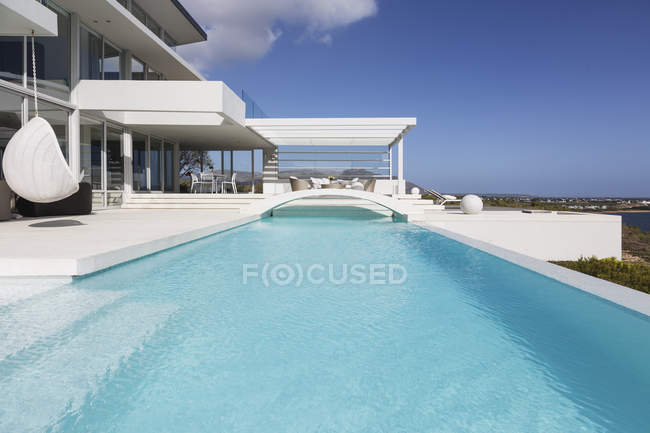 Sunny, tranquil modern luxury home showcase exterior swimming pool and patio — Stock Photo
