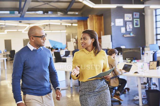 Uomo d'affari e donna d'affari che camminano e parlano in ufficio — Foto stock