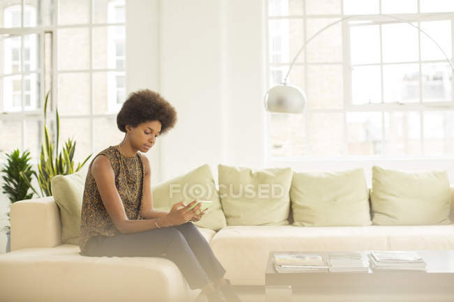 Бизнесвумен, использующая цифровой планшет на диване дома — стоковое фото