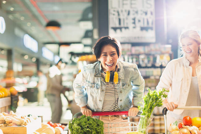 Portrait playful young woman with shopping cart grocery shopping in market — Stock Photo