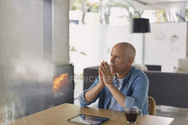 Потрясенный мужчина с цифровой табличкой, пьющий кофе и отводящий взгляд возле дровяного камина — стоковое фото