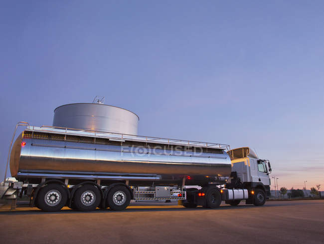 Stainless steel milk tanker next to silage storage tower — Stock Photo