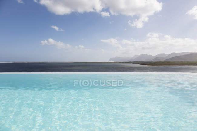 Sunny, tranquil infinity pool with ocean view under blue sky with clouds — Stock Photo