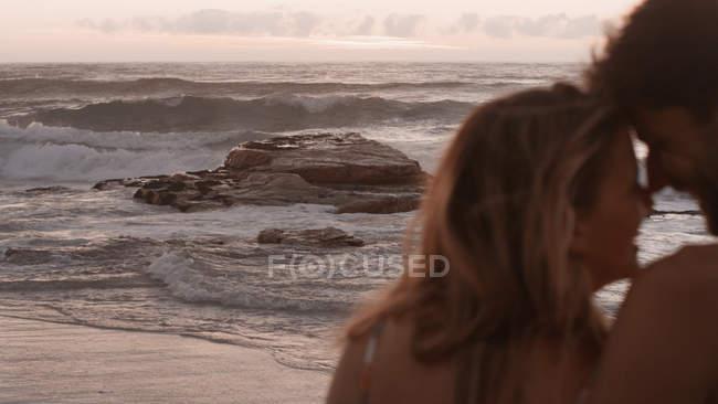 Affectionate couple cuddling on ocean beach — Stock Photo