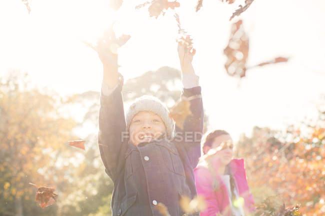 Entusiasta ragazzo che gioca in autunno foglie — Foto stock