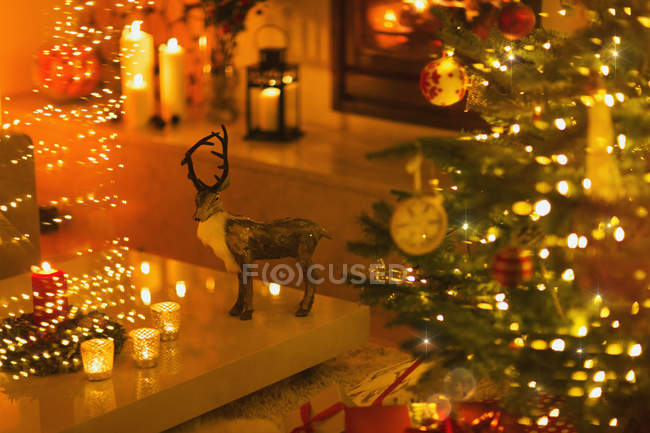 Reindeer decoration in ambient living room with candles and Christmas tree — Stock Photo